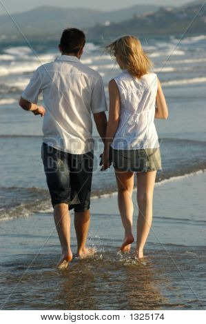 Couple Walking On Waters Edge At Beach