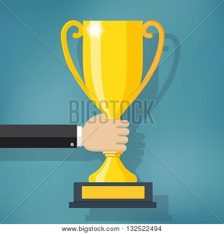 Hand holding a winner trophy cup on the blue background.