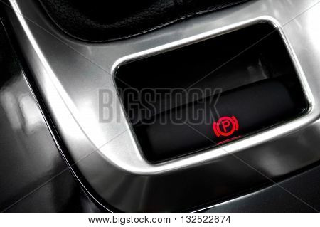 Close-up to a hand brake button in a car.
