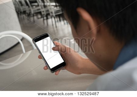 back side of man using smart phone, slice swipe and touch white blank screen in coffee shop. morning city lifestyle checking update news email and interesting feed via social network application. new lifestyle of city working man.