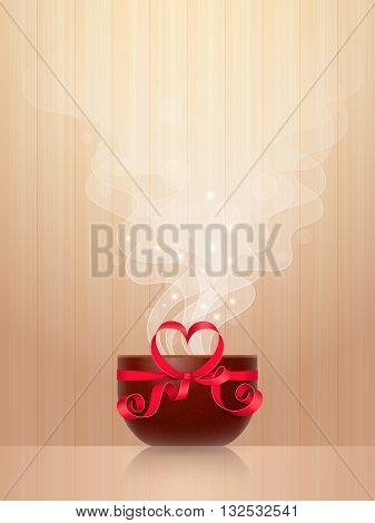 Ceramic cup tied by red ribbon with heart-shaped bow, light steam on wooden background. Favourite drink concept