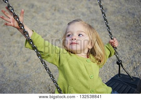 Little child blond girl having fun on a swing outdoor. Summer playground