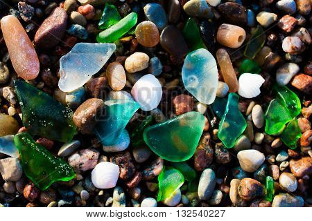 Glass beach. Natural texture with polished sea glass stones and sand