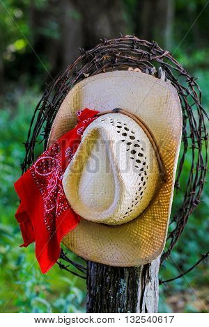 Cowboy hat with red bandana or handkerchief and barbed wire hanging on antique rustic wooden fence post