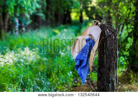 Cowboy hat with blue bandana or handkerchief and barbed wire hanging on antique rustic wooden fence post with grassy road blurred in background