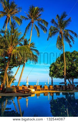 Gorgeous sunset on the beach resort. An oceanfront pool surrounded by palm trees. Palm trees reflected in smooth water