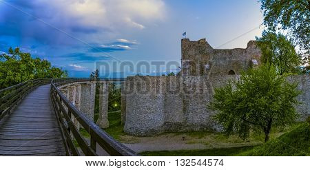 Wooden bridge held by massive rock pillars leads the way into the Neamt fortress, Romania