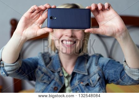 Blonde woman holding a mobile smiling and making a selfie in the room