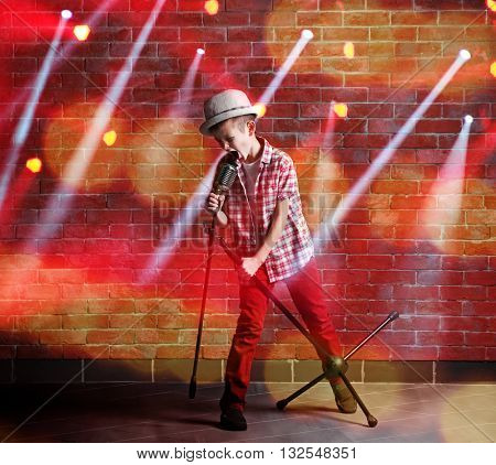 Little boy singing with microphone and laser rays on brick wall background