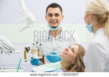 Happy girl in blue shirt and patient bib in the dental cabinet. Near her there is a smiling male dentist and a female assistant. They both wear white uniform with blue latex gloves and blue masks. Dentist also has binocular loupes. He holds an articulator