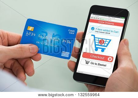 Close-up Of Person Using Credit Card While Shopping On Mobile Phone