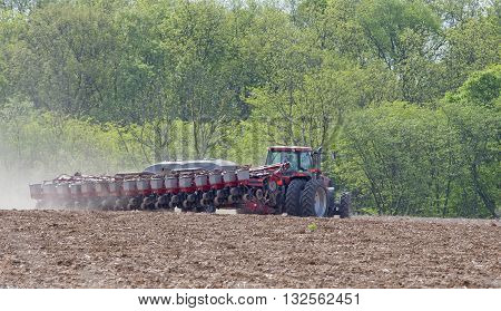 Farm tractor planting seeds in a field