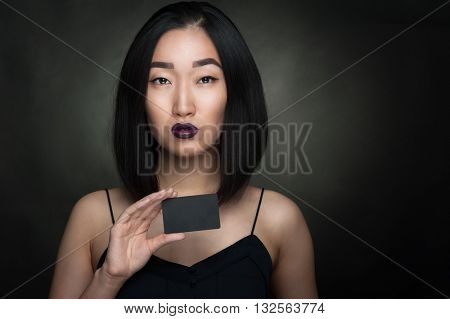 Asian woman hold black empty card