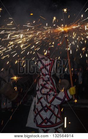 Traditional catalan spectacle called Correfocs (fire runs) or Ball de Diables (Devils' Dance). One of participants dressed as devil and dancing with lighting firework. Reus Spain. Vertical.