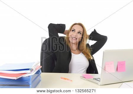 attractive 40s blond businesswoman working at office laptop computer sitting on the desk relaxed and smiling happy as if thinking of vacation isolated on white background business success concept