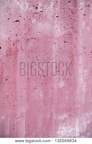 Vesicular rough holey porous stained pink magenta wall close-up background textured