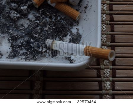 Smoking cigarette in ashtray detailed stock photo