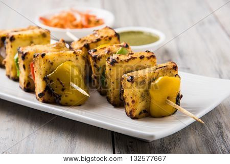 Paneer Tikka Kabab - Tandoori Indian cheese skewers, malai paneer tikka / malai paneer kabab, chilli paneer served in white plate with barbecue stick and green sauce, selective focus