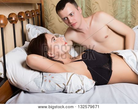young upset couple lying separate in a bed, having conflict problem. sad negative emotions concept, top view. Problem of relations between men and women.