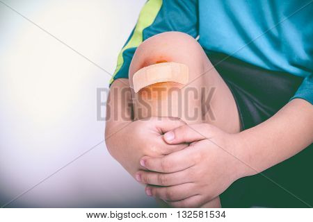 Athlete Child Injured. Child Knee With A Plaster And Bruise. Vintage Style.