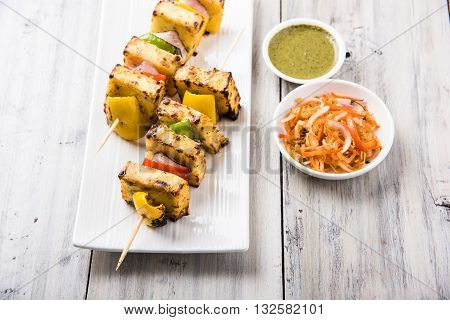 Paneer Tikka Kabab - Tandoori Indian cheese skewers, malai paneer tikka / malai paneer kabab, chilli paneer served in white plate with barbecue stick and colourful capsicum and onion, with green sauce