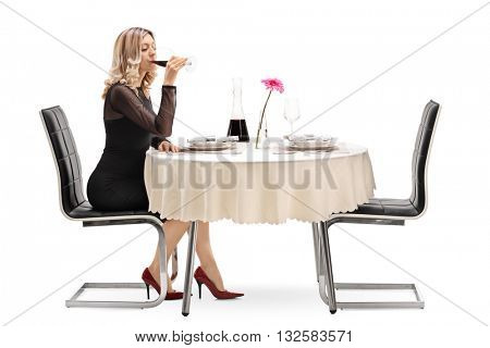Studio shot of a woman drinking and enjoying in a glass of fine red wine seated at a restaurant table isolated on white background