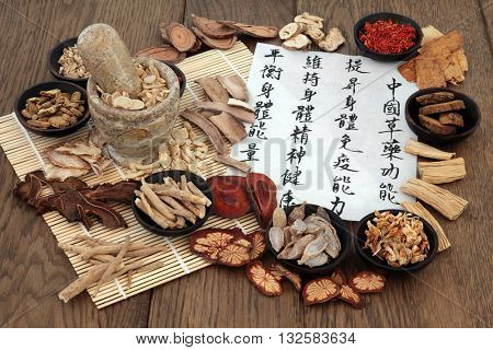 Chinese herbal medicine with herb ingredients and calligraphy. Translation reads as Chinese herbal medicine as increasing the body's ability to maintain body and spirit health and balance energy.