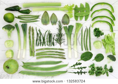 Fresh green super food selection of vegetables and fruits over distressed white wood background, high in antioxidants and vitamins.