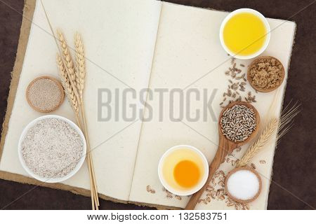 Baking ingredients with brown wholegrain flour, yeast, egg, olive oil, salt sugar and wheat grain  with sheaths on hemp notebook and lokta background.