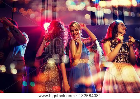 party, holidays, celebration, nightlife and people concept - happy friends dancing in club with holidays lights