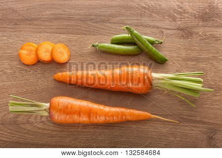 Top view of two whole carrots some carrot's slices and fresh green pea pods on the wooden table