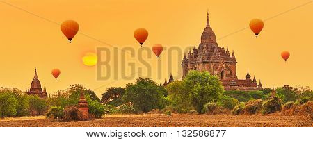 Balloons over Htilominlo Temple at sunrise in Bagan. Myanmar. Panorama
