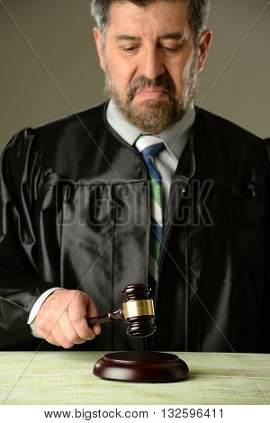 Judge holding a hammer making a verdict against a gray background