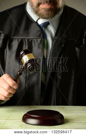 Judge holding a hammer against a gray background