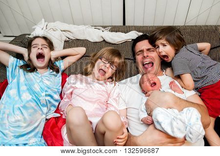 A father his three daughters and baby boy lean back on the couch with open mouth screams. If you can't beat them join them.