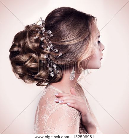 Beautiful bride with fashion wedding hairstyle - on beige background.Closeup portrait of young gorgeous bride. Wedding. Studio shot.