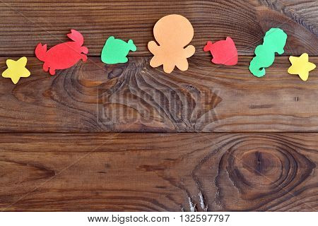 Crab, octopus, fish, starfish - marine life cut from colored paper. Wooden background with colorful paper sea animals. Children creative background. Kids color art background.