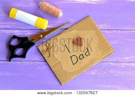 Greeting card with text I love dad. Handmade fathers day card. Scissors, glue stick, beige thread, a needle. Papercraft inspirations. Creative idea for kids. Purple wooden background