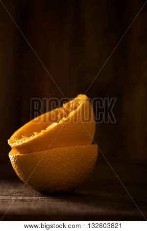 Two Squeezed Orange Halves Standing on Brown Wood