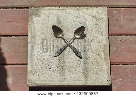 two crossed big spoons on concrete and wood floor