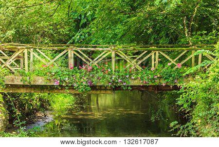 Old Small Bridge Over River In Green Garden.