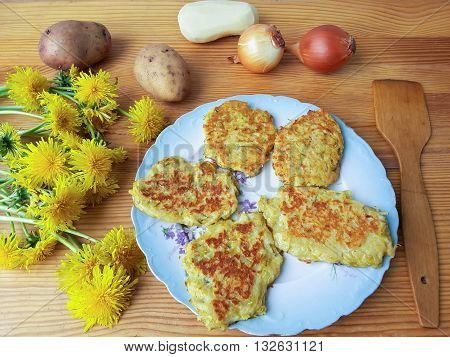 Dandelions flowers with potatoes and onion burgers on plate, organic food