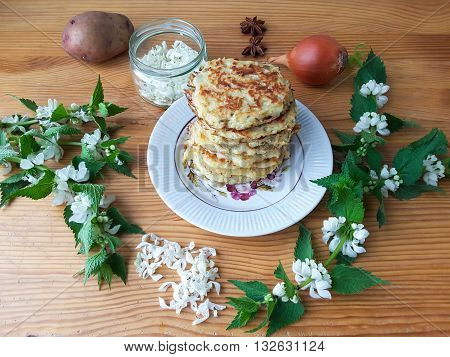 Nettles flowers with potatoes onion and spices burgers on plate, organic food
