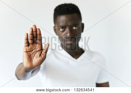 Isolated Shot Of Serious African Male Showing Stop Sign With His Open Palm, Saying That You Better S