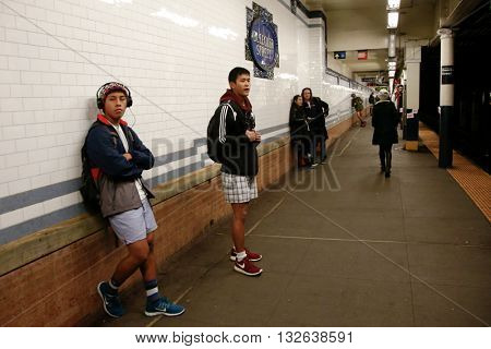 NEW YORK-JAN 12: Participants in the 13th annual international 'No Pants Subway Ride' wait for the uptown 6 train at Bleecker Street on January 12, 2014 in New York City.