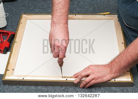 Craftsman working on frame in frame shop. Professional framer hand holding frame angle. Copy space. Top view.