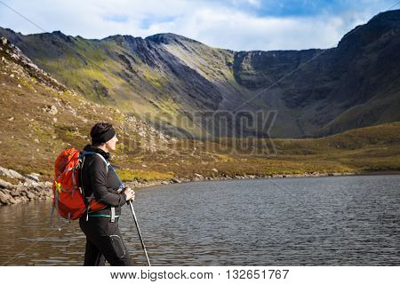 Female Hiker Looking Towards The Mountains At A Lake