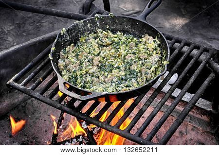 Sausage and spinach egg scramble cooked on a campfire in cast iron skillet