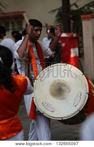 Pune India - September 17 2015: A hindu guy playing the traditional percussion instrument Dhol during a Ganesh festival procession