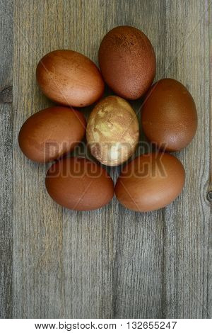 seven painted Easter eggs on a wooden background